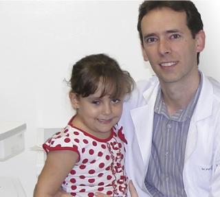 A garotinha Vitória Maria de Paula Barbosa no colo de Dr. Patrick Reis Morais.