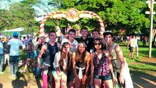 Grupo de amigos na entrada do festival. Ao fundo o símbolo do Tomorrowland.