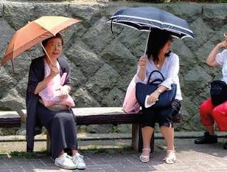 Japonesas usando sombrinhas, um hábito que protege a pele.