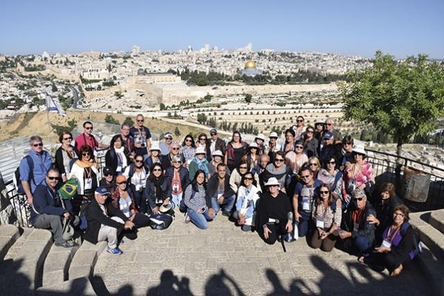 Os peregrinos posam com JerusalÃÆ'Ã'©m ao fundo.
