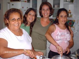 Izabel cozinhando com a filha Neila; atrás, a neta Thatthyanna e a outra filha, Renata.