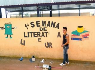 Jonathan Mendes Reis, aluno do primeiro ano do ensino médio, ajuda a pintar o muro da escola com o tema da I Semana de Literatura e Cultura.