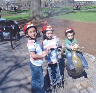 Os meninos num dos sÃÆ'Ã'mbolos bucÃÆ'Ã'³licos de Boston, os famosos patinhos de bronze.