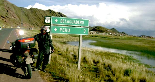 Arlindo Gomes Paulino, 69 anos, ao lado de sua moto às margens do Rio Desaguadero, na fronteira entre a Bolívia e o Peru.