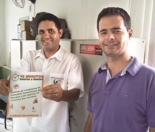 Gabriel Patrick de Jesus Abreu (com o folder) e o diretor do Departamento de Saúde Coletiva, da Secretaria de Saúde de Passos, Michael Silveira Reis.