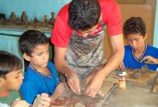 Crianças participam da aula de artesanato, uma das atividades psicopedagógicas.