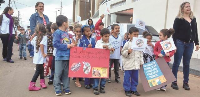 Alunos durante passeata de conscientização contra a dengue.