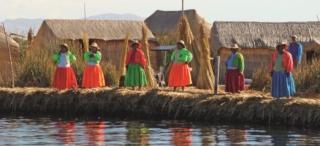 Mulheres se despedindo da gente com as casas de junco ao fundo que são mudadas de lugar a cada 2 sema- nas com o objetivo de forrar com junco seco para controlar a umidade evitando doenças.