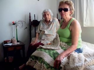 """Defi ciente visual cuida da casa e da mãe de 92 anos A dona de casa Maria Dilza Teixeira, de 71 anos, é cega há aproximadamente 40 anos. Aos 22 anos ela perdeu a visão do olho direito. Na casa dos 30, ela já não enxergava também com o outro olho. Mas ela convive bem com essa defi ciência, porque, segundo diz, suas vistas não eram boas desde criança. """"Com sete anos de idade eu pus óculos de 22 graus�, recorda, contando que a cegueira mesmo começou com o descolamento da retina, quando ela estava grávida do segundo fi lho. """"Tentei operar, mas desisti por orientação das irmãs de caridade do hospital (em Belo Horizonte)�, disse. Sem enxergar nada, Dilza dá conta da casa: arruma, lava, passa, cozinha, faz crochê e ainda cuida da mãe, a cabeleireira aposentada Nely Duarte Teixeira, de 92 anos. """"Nunca fi z promessa para Santa Luzia (a padroeira dos cegos). Aceitei a perda da visão e desde o primeiro momento comecei a treinar, escolhendo feijão�, relembra uma atitude sua para se manter ativa, o que ocorre até hoje. Dilza é membro da Rev-Ver e também considera importante a união dos defi cientes pelo bem de todos. """"Lá é só alegria! Todo mundo conversa, todo mundo dá risada�, disse, completando que a cegueira não é de todo ruim: """"Eu sou feliz em ser cega, porque sou muito paparicada. Se eu voltar a enxergar, ninguém vai ligar mais para mim (brinca)�."""